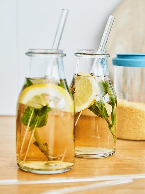 Zwei Glasflaschen mit Infused Water aus Zitrone und Minze