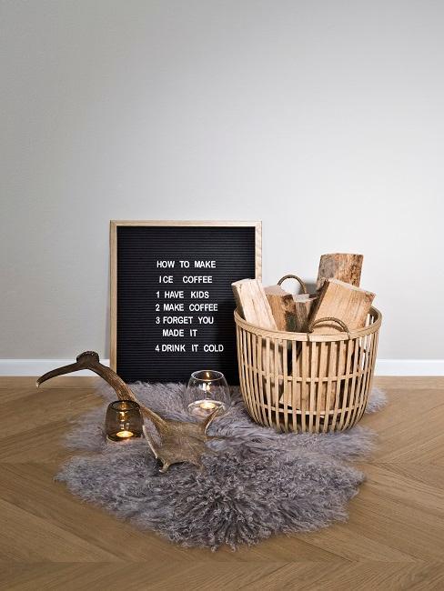 Korb Deko mit Holz auf Fellteppich neben Bild und Deko