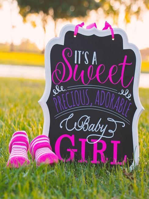 """Schild """"It´s a sweet baby girl"""" auf einer Wiese neben pinken Schuhen als Geschenk zur Geburt"""