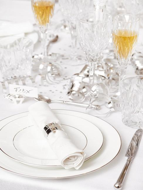 Gedeckter Tisch mit Serviettenringen in Silber und passend dazu Luftschlangen und Konfetti, sowie eleganten Kristallgläsern