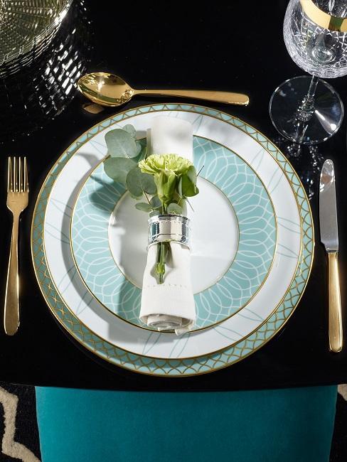 Gatsby Silvester Tischdeko durch grafisch gemusterte Teller und goldfarbenes Besteck, dazu Samtstühle in Türkis und edle Kristallgläser, Blumen an den Serviettenringen runden die Deko stilvoll ab