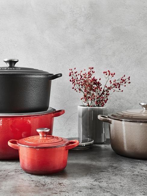 Skandinavische Küche mit roten und schwarzen Töpfen vor grauem Hintergrund