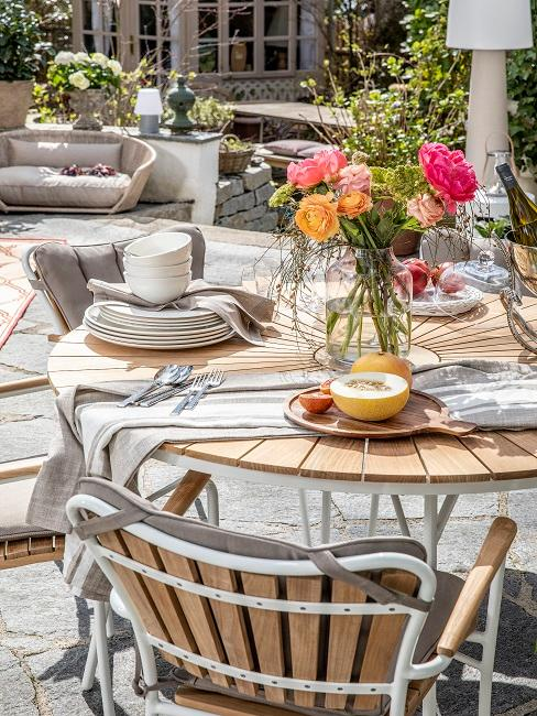 EIne große Terrasse mit rundem Tisch, darauf bunte Sommerblumen als Deko