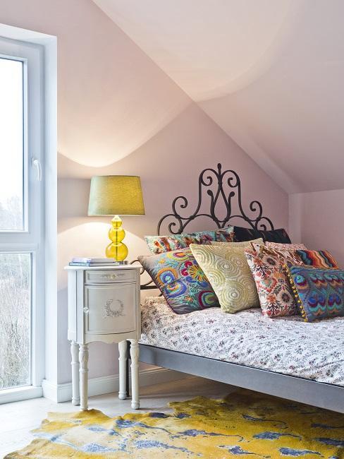 Schlafzimmer Farben: Rosa Wände, gelber Teppich, gelbe Lampe und Bett mit bunten Kissen