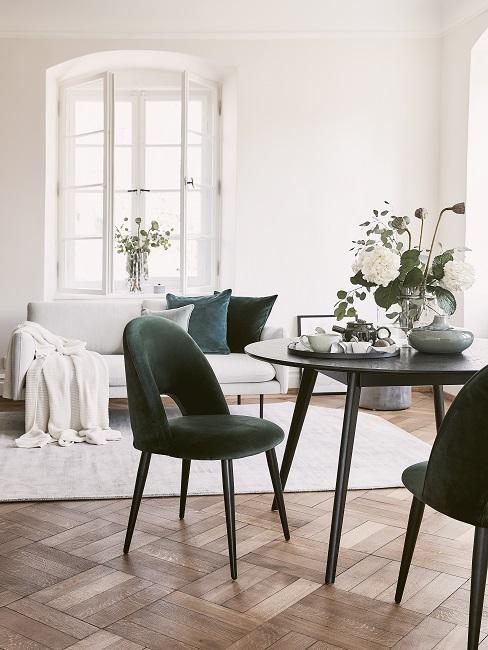 Ein kleiner runder Tisch mit zwei Stühlen gegenüber dem hellen Sofa mit Teppich im Wohn Esszimmer