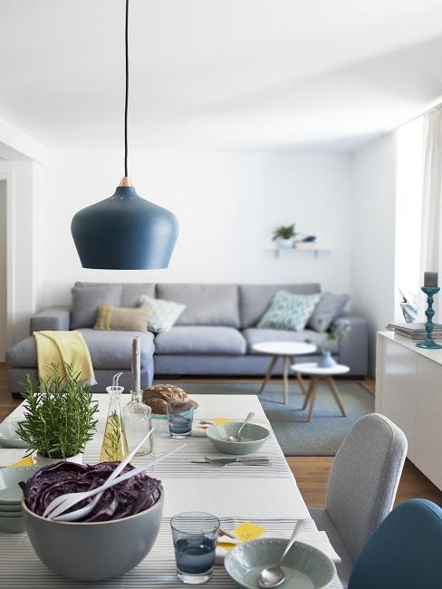 Ein langer gedeckter Esstisch, im Hintergrund am anderen Raumende im Wohn Esszimmer ein großes Sofa in Grau mit Teppich und Couchtischen