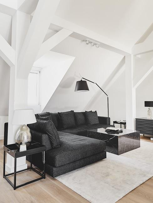 Ein dunkles Ecksofa mit schwarzem Couchtisch in Marmoroptik auf einem hellen Teppich in einer Männerwohnung