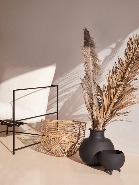 Ein Sessel in Schwarz mit hellem Polster neben einem Holzkorb und einer schwarzen Bodenvase mit getrocknetem Palmenblatt