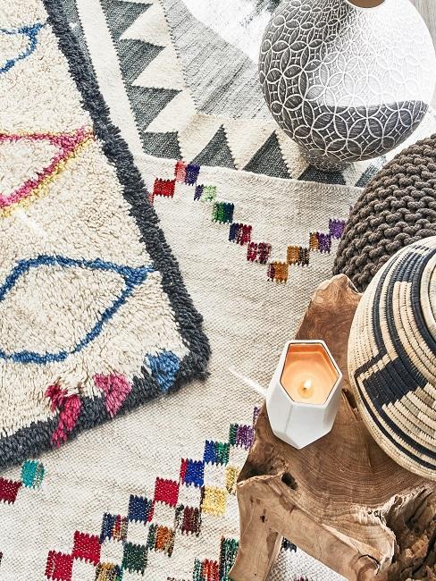 Viele Bohemian Muster Teppiche übereinander, darauf ein Holztisch mit Deko und ein Strick Pouf sowie eine Vase