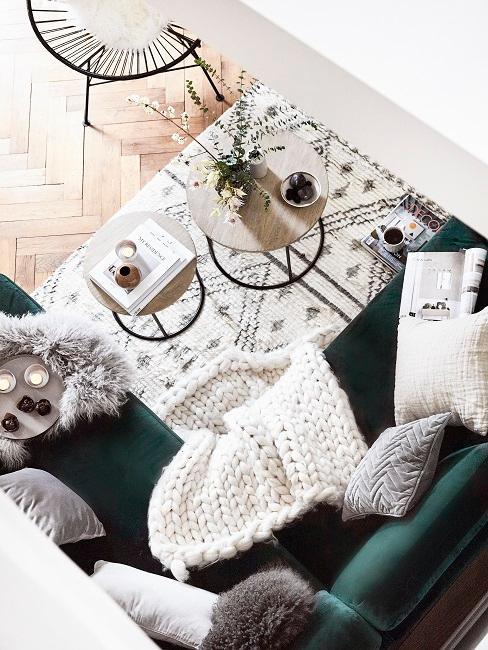 Sitzecke mit einem Sofa in Grün aus Samt, darauf Kissen und eine Strickdecke und davor ein Teppich in Weiß mit schwarzem Ethno Muster im Boho Stil