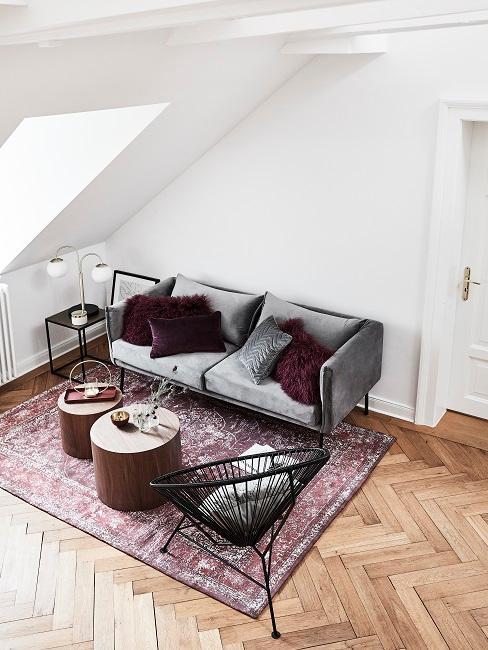 Wohnzimmer mit einem grauen Sofa unter der Dachschräge, dazu ein Boho Vintage Optik Teppich in dunklem Rot und zwei runde Holztische
