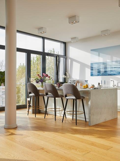 Offene Küche an einer Luxus Fensterfront mit großem Tresen und Barhockern