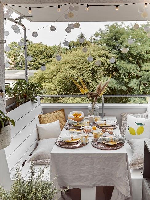 Sitzecke mit zwei Bänken und einem Tisch mit Kissen, Deko wie einer Vase, Lichterketten und Pflanzen
