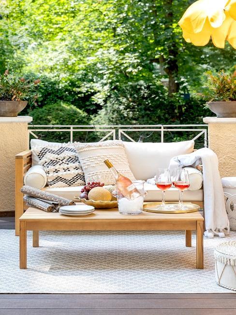 Eine Holzbank auf einem Balkon mit dekorativen Kissen, einem Teppich und einem gedeckten Holztisch
