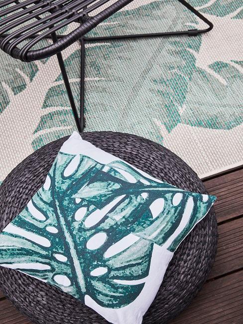 Kissen mit Monstera Motiv auf einem Rattan Pouf, der zwischen dem Holzboden und einem Balkonteppich mit Blattmuster steht