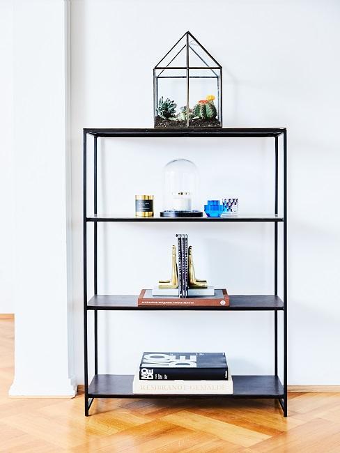 Schwarzes Metallregal mit Büchern und Deko Objekten mittig angeordnet