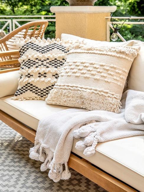 Helle, natürliche Dekokissen und Decke auf Loungemöbel im Garten