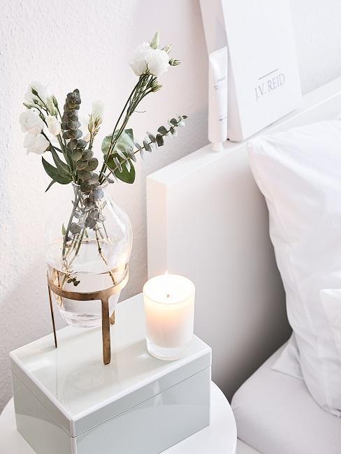 Frühlingsdeko im Glas mit weißen Blumen auf dem Nachttischchen.