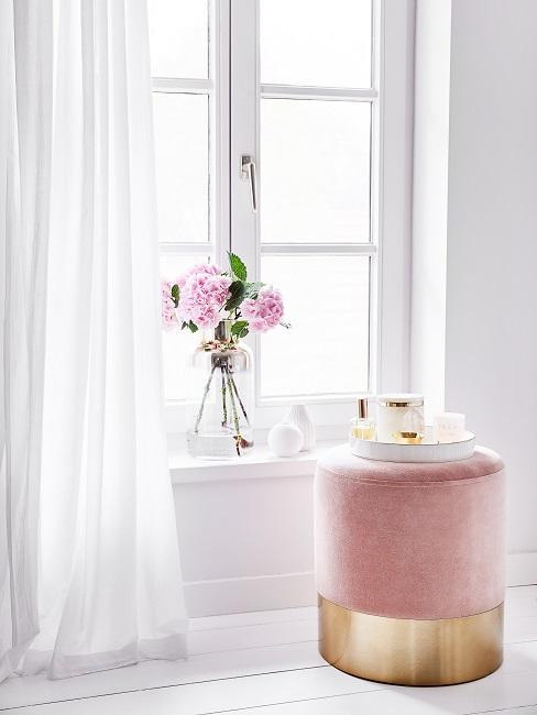 Frühlingsdeko im Glas mit rosa Blumen am Fenster.