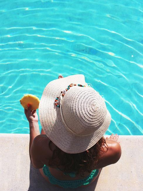 Frau mit weißem Hut im Pool