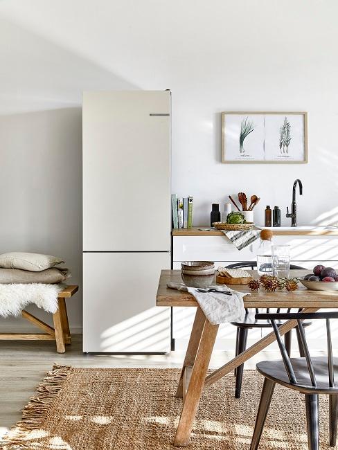 Skandinavische Küche mit Juteteppich, Holztisch und großem weißen Kühlschrank