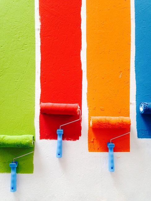 Farbroller mit bunten Wandfarben an Wand