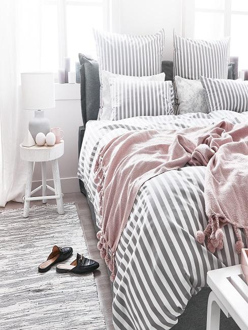 Schlafzimmer mit grau-weiß gestreifter Bettwäsche