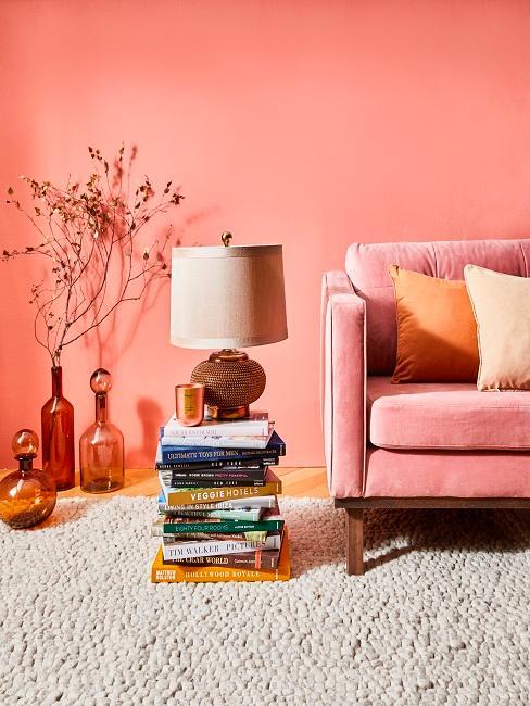 Wandfarbe Altrosa hinter rosa Sofa mit orangenen Kissen und orangenen Vasen