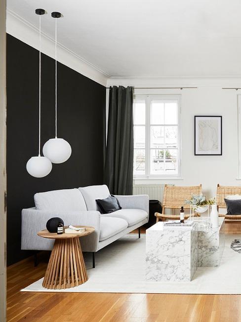 Wohnzimmer mit schwarzer Wandfarbe, weißem Sofa, Teppich und Leuchten, Marmortischen und Rattanstühlen