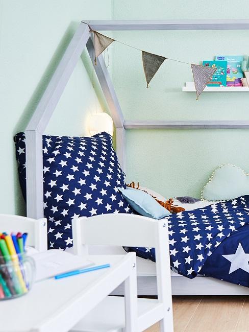 Grüne Wandfarbe im Babyzimmer mit Bett und blauer Bettwäsche