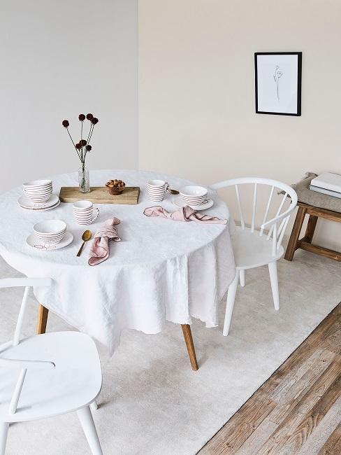 Weiße Wände im Esszimmer mit weißen Stühlen, Teppich und rundem Holztisch