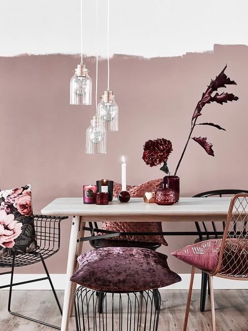 Rosafarbene Wand in Esszimmer mit Holztisch, schwarzen Stühlen und Deko in Lila und Bordeauxrot