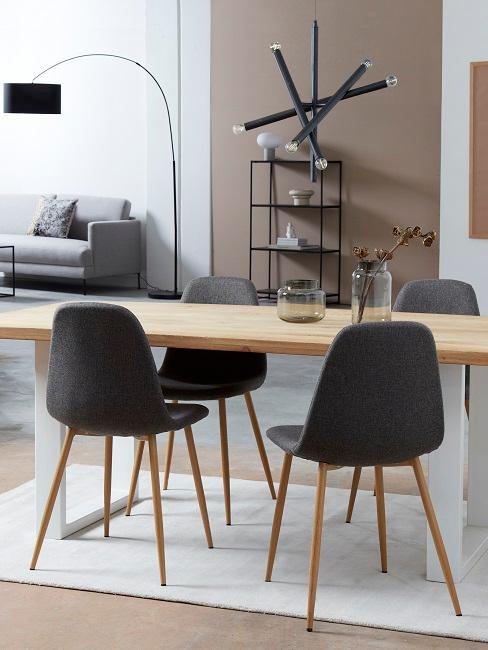 Wohn-Esszimmer mit beigefarbener Wand, hellem Holztisch, dunklen Stühlen und weißen Teppich