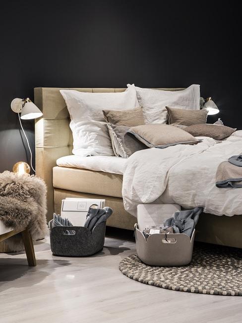 Schwarze Wand im Schlafzimmer mit beigefarbenem Bett, weißer Bettwäsche und Leuchten