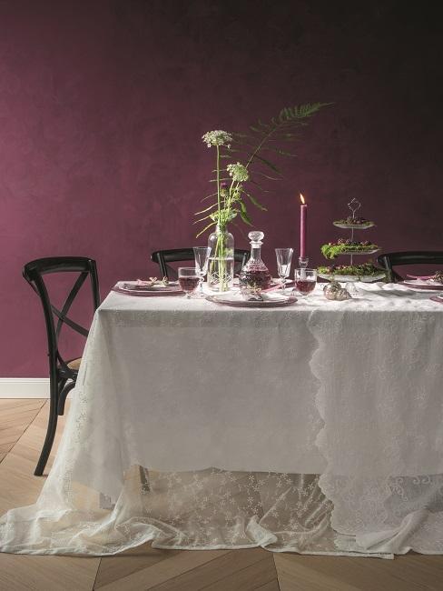 Dunkle Wandfarbe Aubergine im Esszimmer mit schwarzen Stühlen und Tisch mit weißer Tischdecke