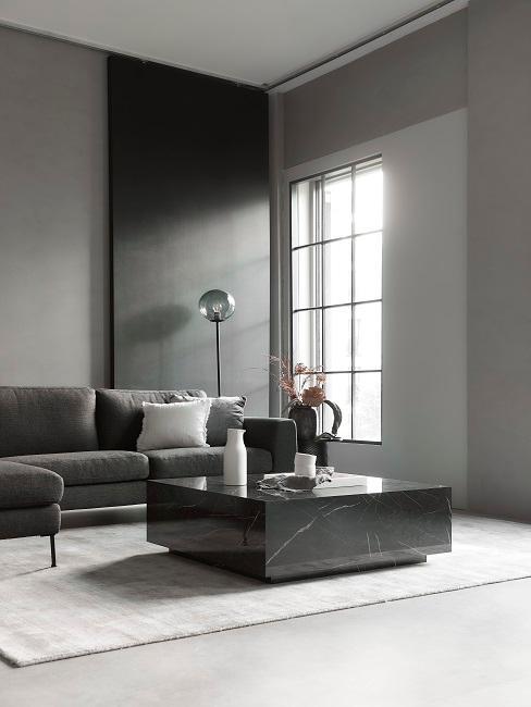 Dunkle Wandfarbe Grau im Wohnzimmer mit schwarzen Marmortisch und dunkelgrauem Sofa