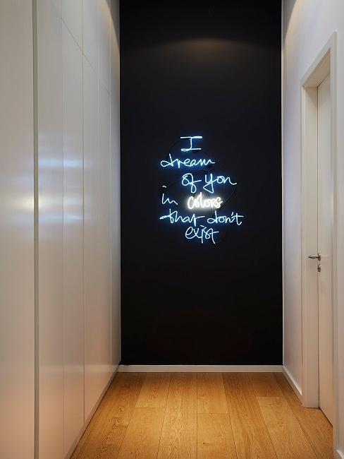 Schwarze Wand im Flur mit Leuchtschriftzug