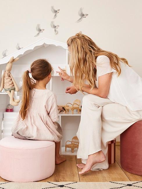 Frau erklärt Mädchen Ordnung im Kinderzimmer vor weißem Regal