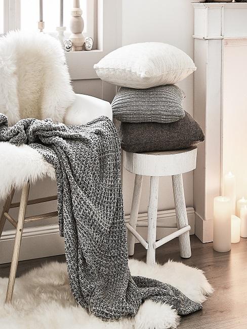 una silla y un taburete blanco con decoración textil: una piel blanca, una manta gris y unos cojines pequeños