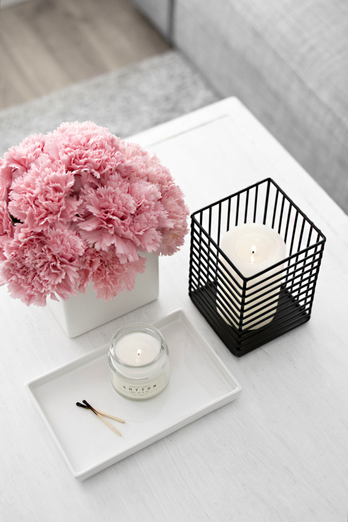Mesa blanca con velas y flores rosas