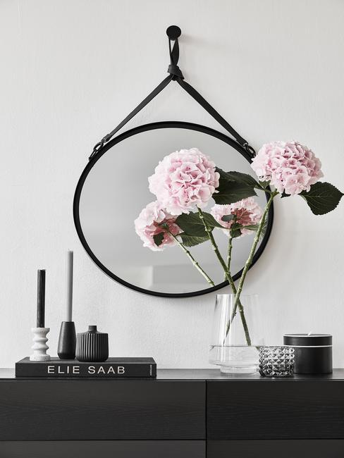 Fleurs roses sur une commode noire devant un miroir