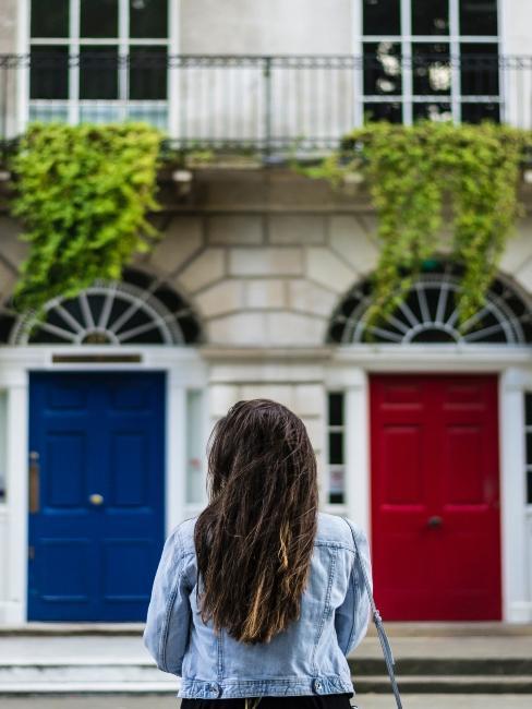 Femme de dos devant deux façades de maisons porte rouge et porte bleue