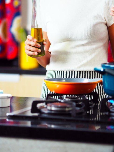Vrouw staat met olie voor een pan