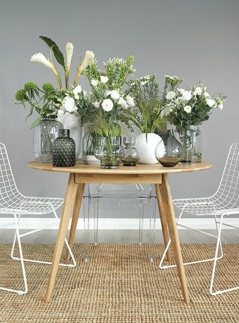 Houten tafel voor grijze wand met witte bloemen in witte vazen