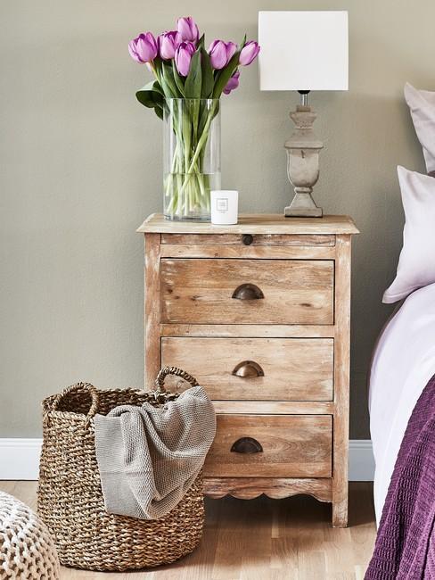 Drewniana szafka nocna z wazonem kwiatów oraz pleciony kosz stojący przy łóżku