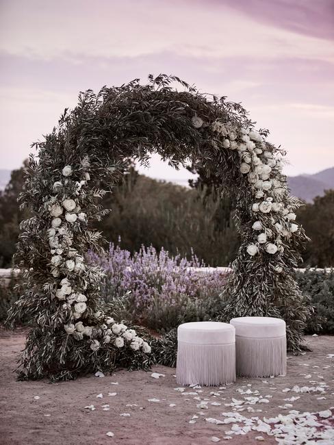 Łuk ślubny stworzony z kwiatów przed którym stoją dwa białe pufy