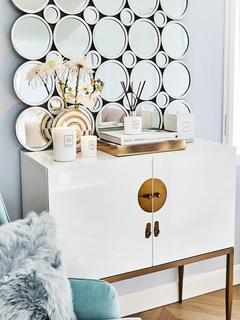 Biała komoda ze złotymi nogami oraz złotymi dekoracjami w salonie w stylu glam