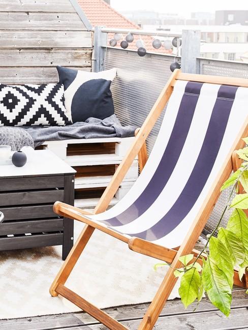 Zbliżenie na leżak z biało-niebieskie paski oraz sofę wykonaną z palet na tarasie na dachu
