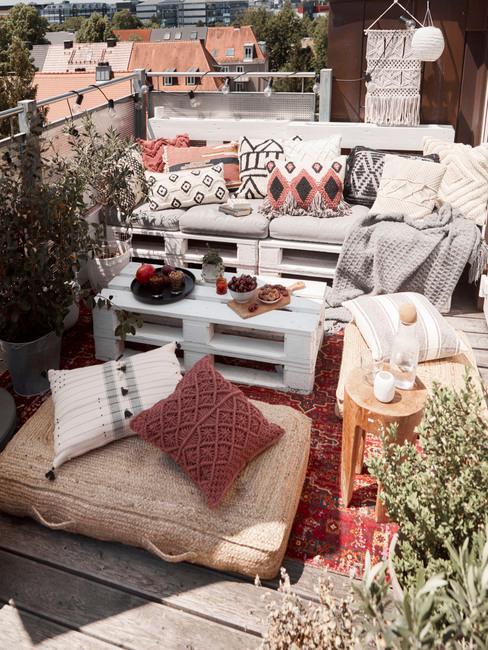 Taras w blodku w stylu boho z sofą oraz stolikiem z palet, czerwonym dywanem, plecionymi pufami oraz dekoracjami