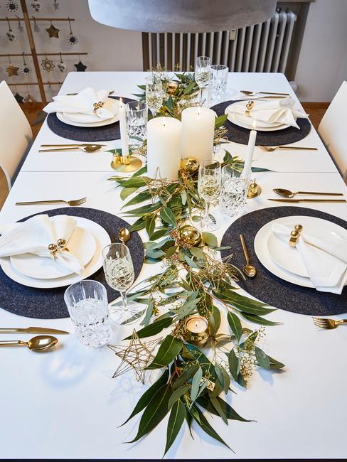 Zastawiony stół z białym obrusem, świeczkami oraz roślinami